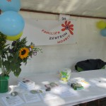 Bild: der Stand des Familienzentrums Moabit-Ost. Auf dem Tisch div. Prospekte, im Hintergrund das Banner mit Logo.