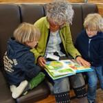 Bild: Großmutter sitzt mit ihren 2 Enkeln auf Sitzbank in eine Bibliothek