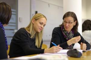 Bild: 3 Frauen sitzend am Tisch, linke hört zu, mittlere schreibt und rechte erläutert mit Gestik