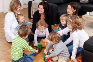 Bild: 3 Frauen sitzen mit 5 spielenden Kindern und einem Baby auf dem Fußboden und unterhalten sich