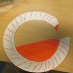 Bild: Ein aus einem Pappteller gebastelter Schwan auf einer Holztischplatte