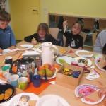 Bild: Kinder und Erwachsene sitzen um einen Tisch und basteln gemeinsam. Getränke, Obst und Kekse in der Mitte.