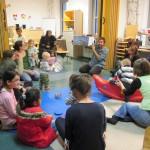 Bild: Babys, Kinder und Erwachsene sitzen auf dem Fußboden des FZM im Kreis. Mitarbeiter der Kurt-Tucholsky-Bücherei hält ein Buch mit Bildern hoch und in die Runde.