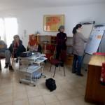 Bild: Blick in einen Raum - Kursteilnehmer sitzen im Kreis und folgen den Ausführungen einer anderen Teilnehmerin am Clipboard. Ein Projektor steht in Mitte des Raumes