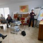 Bild: Blick in einen Raum - Kursteilnehmer sitzen im Kreis und folgen den Ausführungen der Dozentin am Clipboard. Ein Projektor steht in Mitte des Raumes