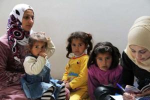 Bild: 2 kleine Mädchen sitzen zwischen zwei syrischen Frauen mit Kopftuch. Ein weiteres Mädchen nuckelnd auf dem Schoß der linke Frau. Rechte Frau macht Notizen.