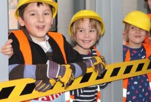 Bild: Kinder in Bauarbeiterkleidung stützen sich mit den Oberarmen auf einer Absperrung ab. Blick in Richtung Betrachter.