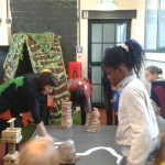 Bild: Kinder bauen auf einem Tisch Häuser aus kleinen Holzbauklötzen