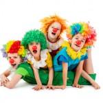Bild: 3 Jungs mit roten Clownsnasen und bunten Perücken liegen bauchseitig auf dem Rücken eines 4. Jungen. Alle Blick zum Betrachter.