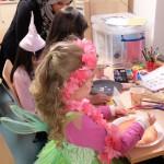 Foto: 3 Mädchen bemalten je einen Pappteller für Masken auf einem Tisch. Am hinteren Tischende junge Frau mit Kopftuch erklärt. Blick von seitlich und hinten.