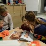 Foto: Mutter schminkt das Gesicht ihres Kindes nach davor auf dem Tisch liegender Buchvorlage. Andere Mutter links danaben am Tisch schaut mit ihrem Kind zu.