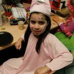 Foto: Mädchen mit blumenbemaltem Gesicht und Spitzmütze sitzt quer zwischen Tisch und Stuhllehne und blickt zum Betrachter.