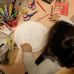 Foto: kleines Mädchen bemalt einen Pappteller für eine Maske. Blick von hinten und oben.