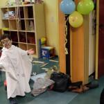 Foto: Kind mit weißem Umhang aus Bettlaken und bemalten Gesicht spukt als Gespenst durch den Raum
