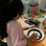 Foto: Kind bemalt einen Pappteller mit Tuschfarben für eine Maske. Blick von rechtsseitig.
