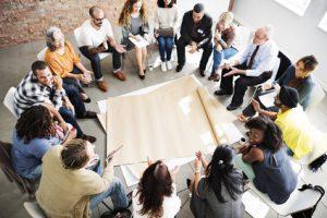 Bild: viele Personen unterschiedlichen Alters und ethnischer Herkunft sitzen im Kreis. Dozent erläutern ...