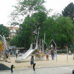 Bild: viele Kinder mit ihren Eltern spieln zwischen Klettergerüsten