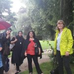 Foto: 5 Frauen im Regen unterm Baum mit Blick zum Betrachter. Ein Frau unter dem Regenschirm