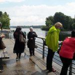 Foto: 5 Frauen am Geländer eine betonierten Seeufers. 2 schauen ins Wasser, eine auf ihr Handy und 2 unterhalten sich.
