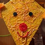 Foto: ein selbsgebauter Drachen aus gelbem Fasermaterial mit rotem Mund und Nase und schwarzen Augen