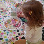 Foto: kleines Mädchen malt auf einem Plastikteller auf einem Tisch. Blick von hinten über die Schulter.