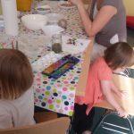 Foto: Eltern unterhalten sihc na einem Tisch, Kinder malen dabei