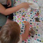 Foto: Kind bemalt Gipsfigur an einem Tisch. Mutter sitzt mit Baby im Arm danaben und erklärt.