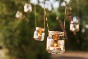 Foto: Teelichter in Gläsern die an Bindfäden frei von Bäumen hängen. Erstes Windlicht scharf - dahinter hängende alle unscharf