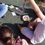 Foto: Kinder und Erzieherin sitzen auf der Erde und fertigen Perlenketten