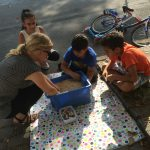 Foto: 3 Kinder und eine Erzieherin knieend und hockend auf dem Bürgersteig vor einer blauen Kiste mit Linsen, in der sich ein Schatz befindet.