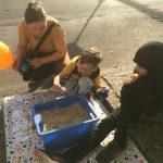 Foto: Eltern und ein Kind hockend und sitzend auf dem Bürgersteig vor einer blauen Kiste mit Linsen, in der sich ein Schatz befindet. Das Kind hat gerade einen Schatz gefunden.