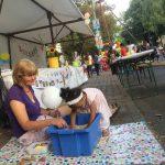 Foto: eine Erzieherin sitzend vor und ein kleines farbiges Mädchen gebeugt über einer blauen Kiste mit Linsen auf dem Bürgersteig, in der sich ein Schatz befindet. Hintergrund: der Stand vom Familienzentrum.