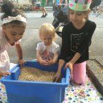 Foto: 3 kleine Mädchen knieend auf dem Bürgersteig vor einer blauen Kiste mit Linsen, in der sich ein Schatz befindet. Die Straße mit Festbesuchern im Hintergrund