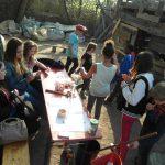 Foto: Viele Jungs und Mädchen sitzen oder stehen an einem Tisch und jeder bastelt etwas, quatscht oder liest. Bretterbude im Hintergrund.