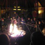 Foto: Kinder und Eltern sitzen im Dunklen um ein Feuerschale und backen Stockbrot.