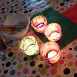 Foto: 4 Windlichter selbst beklebt mit buntem Papier und brennenden Teelichten darin auf einem Tisch (von oben). Glas und Schale mit Pinseln im Hintergrund.