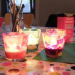 Foto: 4 Windlichter selbst bekelbt mit buntem Papier auf einem Tisch. Glas mit Pinseln und Klebstoffpackung im Hintergrund.