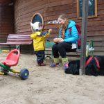 Foto: Kleiner Jung und ein älteres Mädchen unterhalten sich vor einer Holzhütte. Dreirad und großer schwarzer liegender Hunf im Vordergrund.