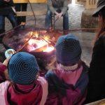 Foto: Kinder, Jugendliche und Eltern sitzen mit Stockbrotspießen vor Feuerschale. Blick von hinten über die Köpfe zweier Kinder.