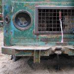 Foto: untere Front eines sehr alten grünen LKW. Linksseitig Bein eines auf der Stoßstange stehenden Kindes.