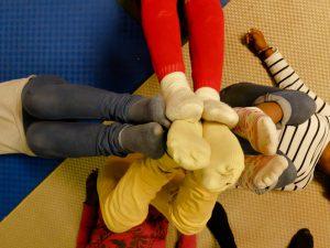 Foto: vier in kreuzform auf dem Rücken liegende Kinder strecken ihre Füße noch oben, in Richtung Betrachter und berühren sich alle an ihren Fußsohlen.