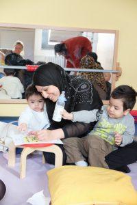 Foto: junge Frau malt mit ihren Kleinkindern auf einem Hocker. Ein Kind auf dem Schoß hält eine Nuckelflasche mit Milch in einer Hand. Spiegel im Hintergrund in dem weitere Mütter mit Kindern zu sehen sind.