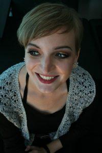Foto: Porträt - junge Frau mit herzlichem Lächen und silbriger Stola über schwarzem Top, blickt nach links. Blick von oben auf Gesicht und Oberkörper.