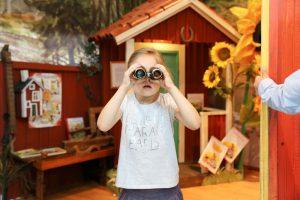 Foto: Mädchen ind der Bildmitte schaut durch ein Fernglas direkt auf den Betrachter. Rotes Häuschen im Hintergrund.