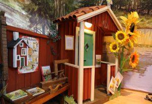Foto: Personen-großes Model des Eingangs eines typisch schwedischen Holzhauses im rote-weißen Stil mit Sonnenblume am Vorbau. Rechts daran eine Bank mit Büchern und Werkzeug.