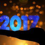 Fotomontage: Silouette einer ausgesteckten Hand, auf der nach oben ausgerichteten Innenseite die Zahlen 2017 in blau stehen. Hintergrund bräunlich-gelb, mit hellen Lichtpunkten.