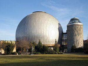 Foto: Silberne Kuppel des Planetariums von außen. Rechts daneben der verbundene Turm.