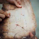 Foto: Finger zeigen etwas auf einer Schatzkarte