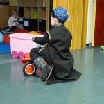 Foto: Kind mit schwarzem Mäntelchen und Kappe auf Dreirad von hinten. Im Hintergrund spielt im Nebenraum ein anderes Kind auf dem Fussboden.