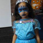 Foto: Mädchen mit blauem Kleid und blauer Bemalung im Gesicht blickt zum Betrachter.